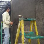 Chris Borton plastering straw bale greenhouse
